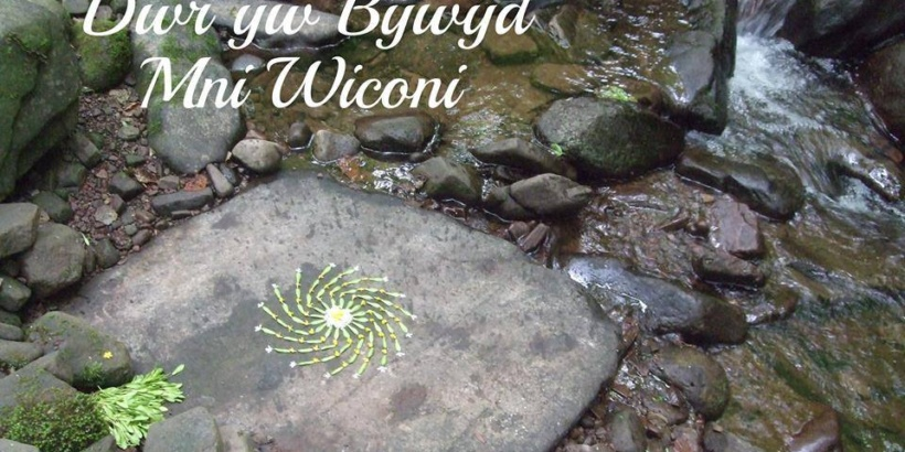 Photo art by Amber Woodhouse of Dwy yw Bwyd -- Water if Life. A spiral sun sign adorns a stream-smoothed rock in a stream with the motto Water is Life