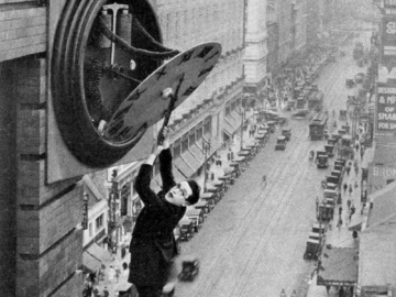Harold Lloyd is hanging from the clock face above Broadway in Los Angeles in his antic climb up the building