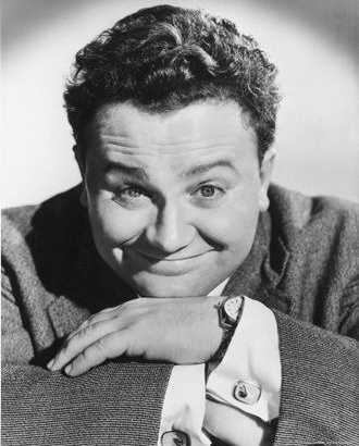 Sir Cumference Harry Secombe aka Ned of Wales, smiling over crossed hands