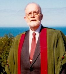 Doctor & Poet Joseph Clancy, bearded with glasses in a suit and tie and academic robe standing by the seaside in Aberwystwyth, Wales